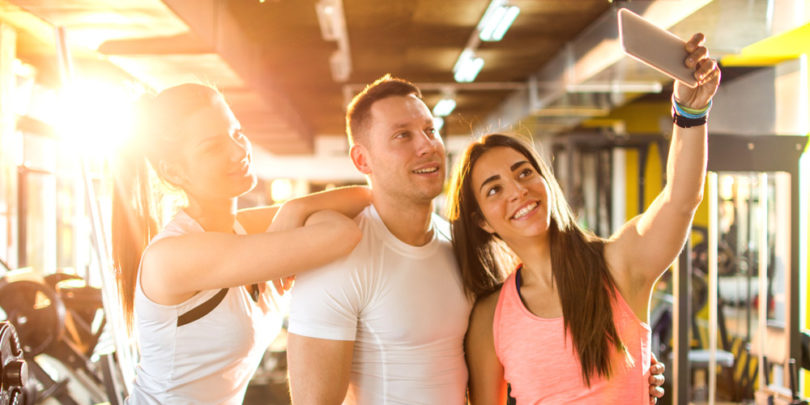 three people taking a selfie in the gym to help with their social media strategy