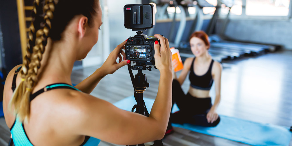 fitness demonstration being filmed by 2 girls in the gym for their fitness brand and marketing strategy